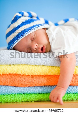 Sleeping baby on colorful towels stack - stock photo