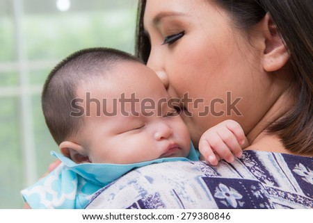 Sleeping baby on the mother's hands. Young mother shakes her baby in her arms. - stock photo