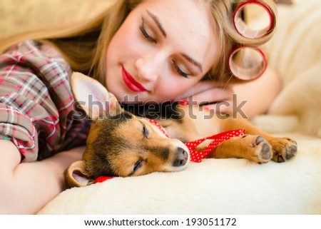 sleeping beauties picture: closeup portrait of pinup girl beautiful blond young woman with curlers having fun sleeping or dreaming with her little puppy dog happy smiling on bed - stock photo