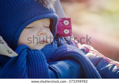 Sleeping beautiful baby boy in blue hat outdoor in winter cold weather. Sweet baby sleeps in a stroller on a walk in the fresh air. Early spring. Toned effect. - stock photo