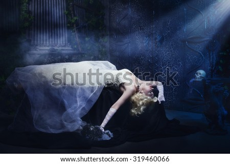 Sleeping Beauty. Beautiful lifeless bride in white dress lying on the shore in a tomb. Dark mystery scene. Low key  - stock photo