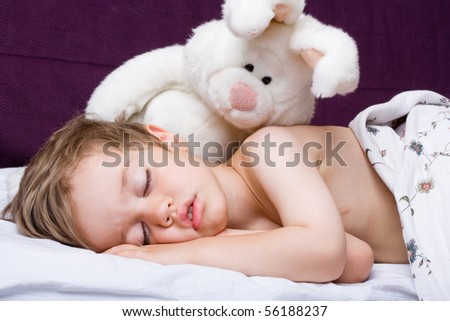 Sleeping boy and rabbit toy. Closeup portrait.