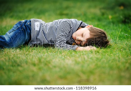 Sleeping boy in a field/grass - stock photo