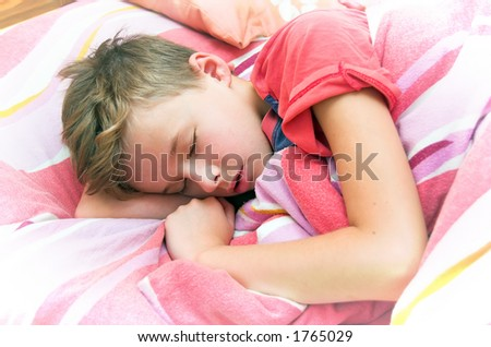 Sleeping boy in bed - stock photo