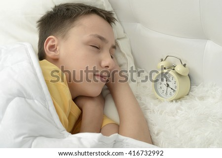sleeping boy with alarm clock