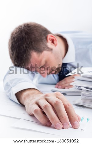 Sleeping Businessman. Tired businessman asleep at office desk full of papers. Shallow depth of field. - stock photo