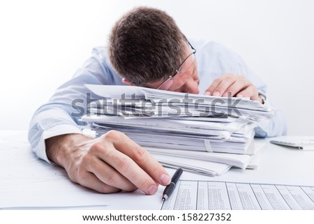 Sleeping Businessman.Tired businessman asleep at office desk full of papers. Shallow depth of field. - stock photo