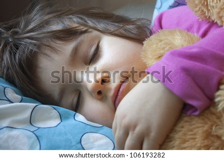 sleeping child in her bed with teddy bear - stock photo