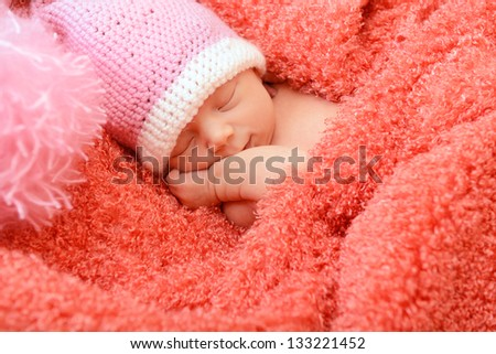 sleeping cute baby funny pink hat in soft fabric and smiling in sweet dreams, beautiful kid's face closeup - stock photo