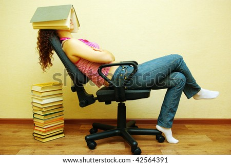 Sleeping female student with book on head - stock photo