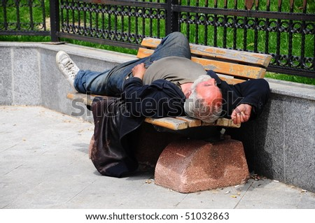 sleeping homeless man on the bench im a park