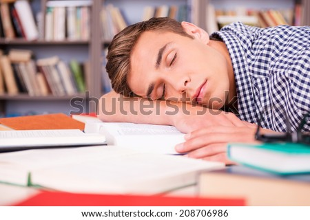 Sleeping in library. Handsome young man sleeping while sitting in library and leaning his face at the desk  - stock photo