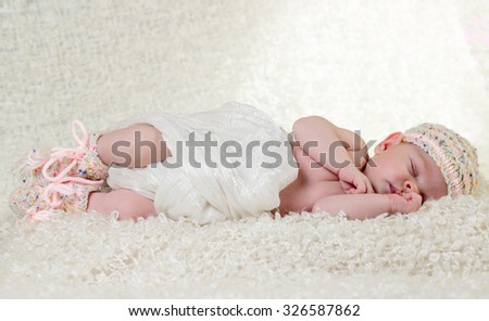 Sleeping infant on white fluffy blanket