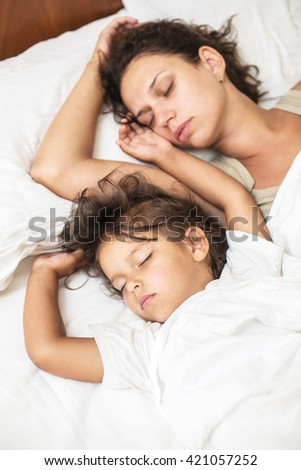 Sleeping kid girl and her mother in the bed.