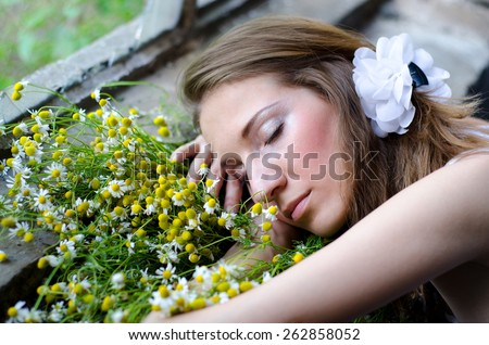 Sleeping lady with chamomile bouquet in spring.