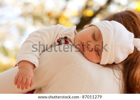 Sleeping little girl on mother's shoulder in autumn park - stock photo