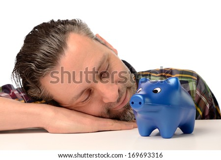 Sleeping man with a blue piggy bank, financial concept - stock photo