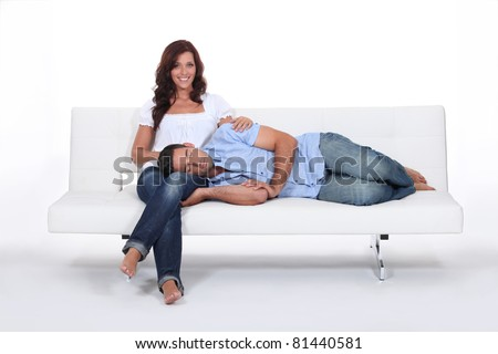 Sleeping man with his head on his girlfriend's lap - stock photo