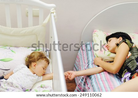 sleeping mother and daughter holding hands - stock photo