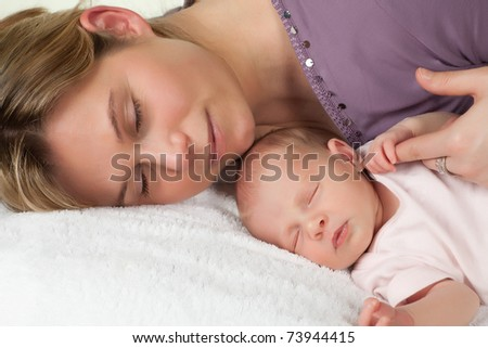 Sleeping mother with her sleeping 18 days old baby - stock photo