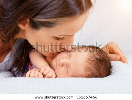 Sleeping newborn baby boy 10 day old with his mother  - stock photo