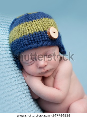 Sleeping newborn baby boy, infant, on a blue knit blanket, posed asleep during nap time - stock photo