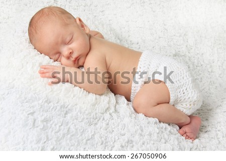 Sleeping Newborn baby boy wearing a knitted diaper cover.  - stock photo