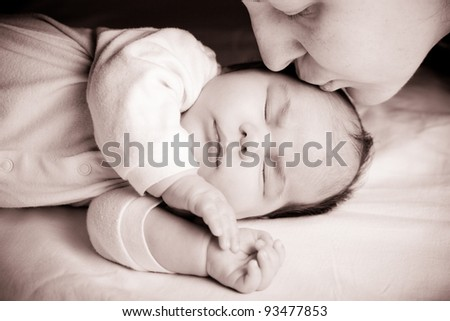 Sleeping newborn baby closeup face with mother kissing - stock photo
