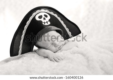sleeping newborn baby in a pirate hat on a white background - stock photo