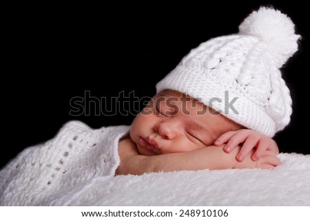 Sleeping newborn baby in a white hat on a white rug. Black background. Tenderness, peace - stock photo