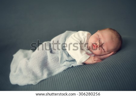 sleeping newborn baby in a wrap - stock photo