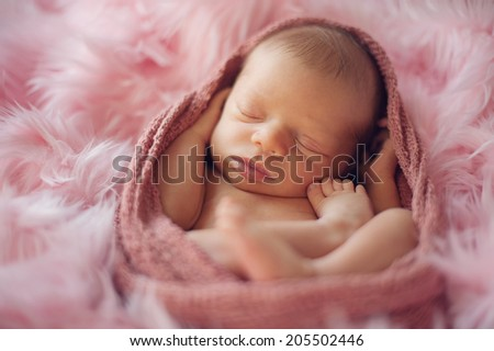 Sleeping Newborn Baby in Pink Wrap - stock photo