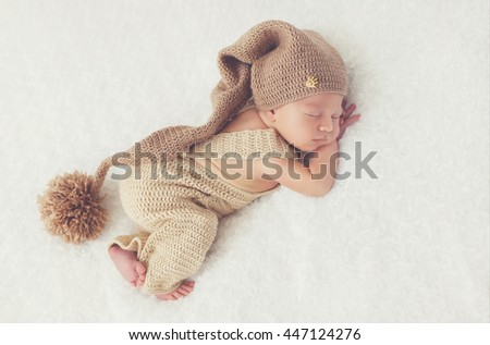 sleeping newborn baby. Sleeping newborn baby on fur with knitted hat. baby girl or baby boy.  - stock photo