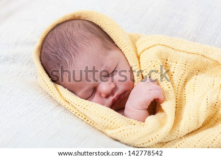 sleeping newborn baby wrapped in a yellow blanket - stock photo