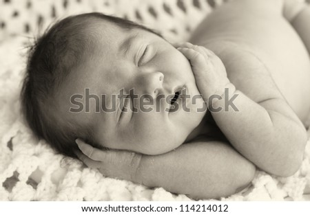 Sleeping newborn girl with hands on face.