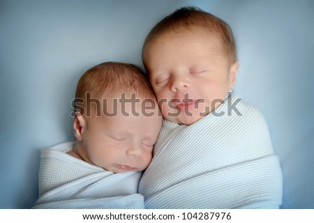sleeping newborn twins, on blue blanket - stock photo
