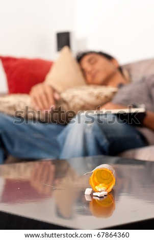 Sleeping Pills on Table with Man Asleep in Background - stock photo