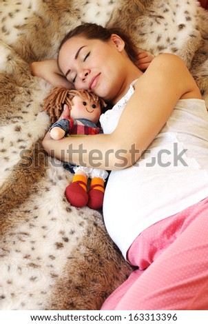 Sleeping pregnant woman on the bed - stock photo