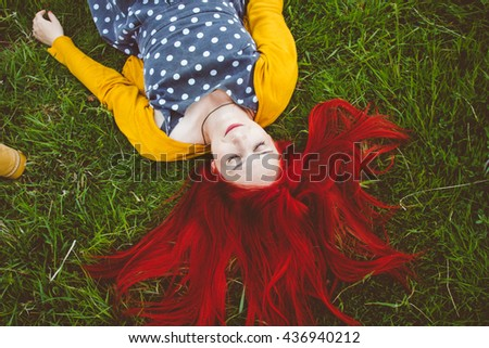 Sleeping red haired beauty, relaxing in the vivid field on leisure time, on a sunny day - stock photo
