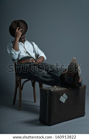 Sleeping retro afro america western cowboy man with mustache. Sitting in wooden chair. Resting his legs on suitcase. Wearing brown hat. Cool tough guy.