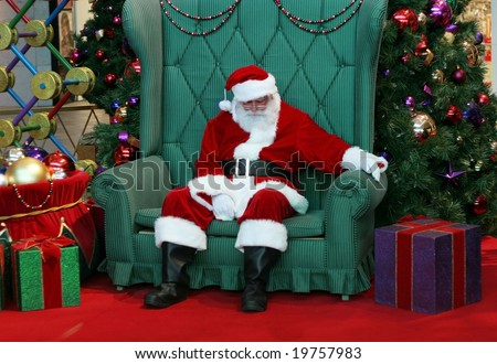 sleeping santa claus in big green chair surrounded by decorations