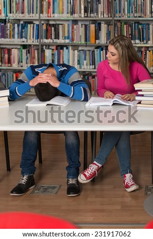 Sleeping Student Sitting And Leaning On Pile Of Books In College - Shallow Depth Of Field - stock photo