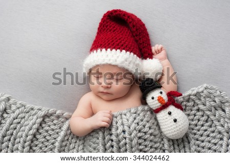 Sleeping, two week old, newborn, baby boy wearing a crocheted Santa hat with snowman plush toy. - stock photo