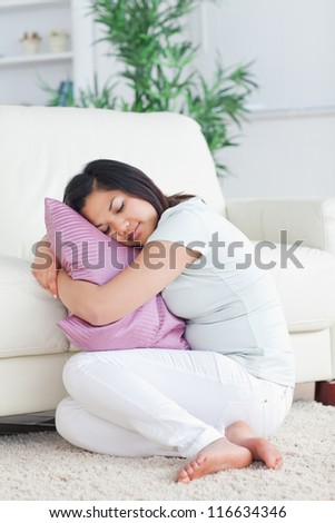 Sleeping woman holding a pillow while sitting on the floor in a living room - stock photo