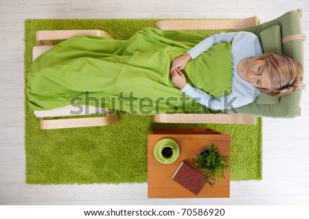 Sleeping woman in armchair covered with blanket in elevated view.?