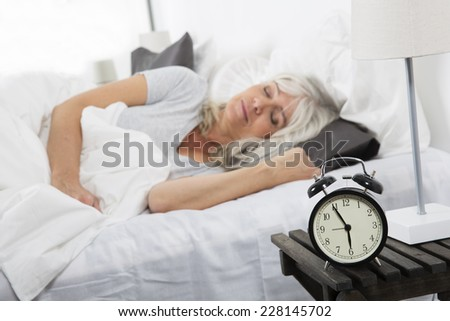 Sleeping woman in front of the alarm clock - stock photo
