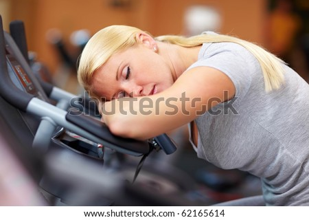 Sleeping woman in gym with her head on a hometrainer - stock photo