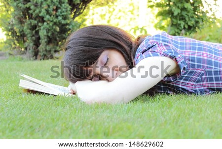 Sleeping woman in the garden after reading a book