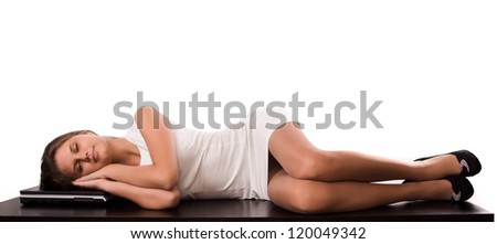 Sleeping young girl lying on the office table - stock photo
