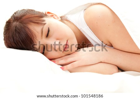sleeping young woman in white bedding, white background - stock photo